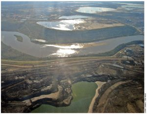 The oil sands and Athabasca River in Alberta as seen through an airplane window's glare. The Athabasca River flows past a tailings pond.