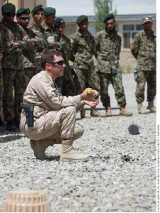Warrant Officer Tim MacCormac demonstrates how to prepare a charge to dispose of unexploded ordnance during a class with Afghan National Army (ANA) soldiers.