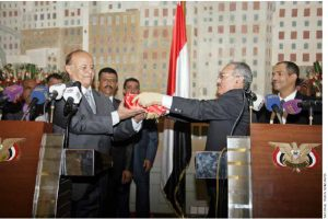 Ali Abdullah Saleh, right, hands Abed Rabbo Mansour Hadi the flag of Yemen.