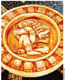 A carved stone Mayan calendar on tile background.