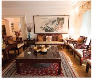 The living room is a simple, bright space, decorated with imposing Chinese rosewood chairs and tables.