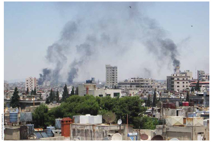 Smoke drifts into the sky from buildings and houses hit by shelling in Homs, Syria, in June.