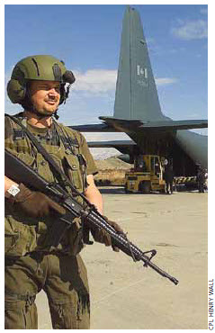 Canadian military policeman Cpl. Eric Belanger stands guard with a C7A1 assault rifle while humanitarian aid is unloaded from a CC-130 Hercules in Afghanistan.