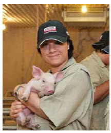 Sonya Fiorini, senior director for corporate social responsibility for Loblaw Companies, holds a piglet on a western Ontario farm.