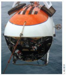 The Mir submersible is hoisted into the water using a cable connected to the ship's winch system. This front view shows the versatile manipulator arms and the huge viewing port.