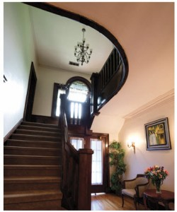 From the central hall, a wooden staircase leads to a tall, leaded-glass window before reaching the second floor and its six bedrooms.