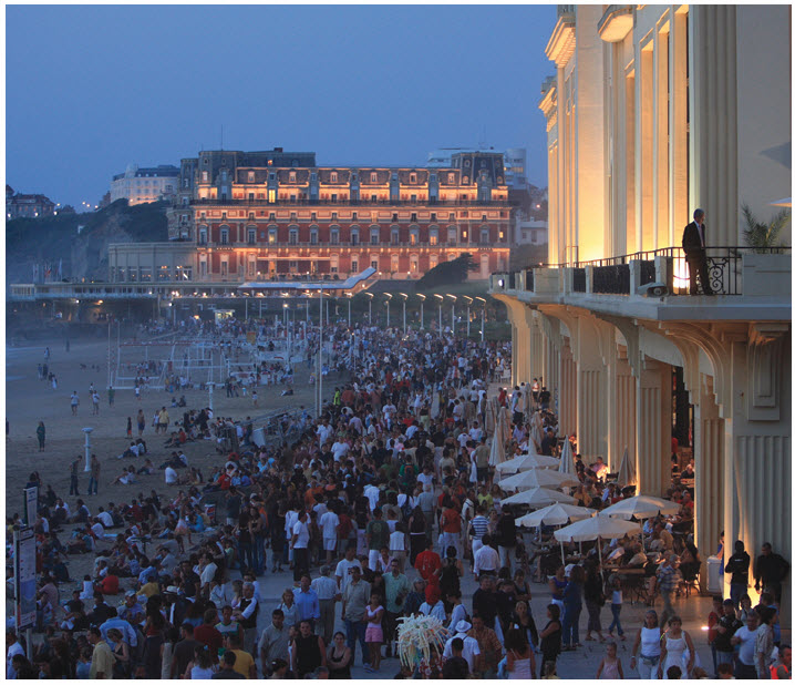 "A Bastille Day celebration at the ""grande plage"" in Biarritz on the Atlantic Coast. On the right, is the casino and in the background, the Hotel du Palais, which Napoleon III originally built for his wife, Empress Eugénie."