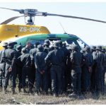 Trainee rangers crowd around a Kruger Park helicopter while the pilot instructs them about how to load and unload.