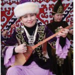 A woman at the Zheruik, an ethno-village in Astana, plays a traditional stringed instrument known as a dombra. (Photo: Ülle Baum)