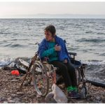 Nojeen, a16-year-old Syrian refugee, who uses a wheelchair due to a balance problem, waits to be lifted to the road. She and her older sister landed on the Greek island of Lesbos after crossing from Turkey, in hopes of finding better medical care. Greek authorities are looking after her. (Photo: © UNHCR/Ivor Prickett)