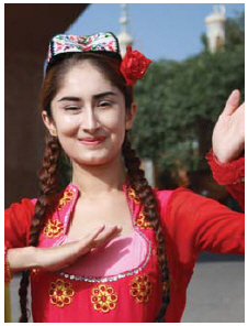 A dancer in brightly coloured traditional dress and handembroidered Uyghur flower hat performs for tourists visiting Kashgar. (Photo: Ülle Baum)