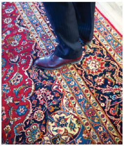 Khan stands on one of the intricately designed carpets, handmade by Pakistani families. (Photo: Ashley Fraser)