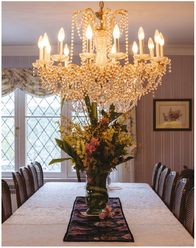 The dining room seats 20 and, while the chandelier strikes a formal, elegant note, the softly striped wallpaper adds warmth. (Photo: Dyanne Wilson)