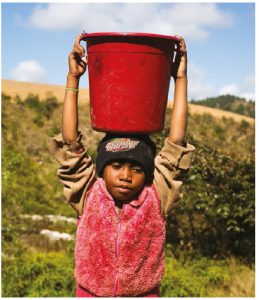 Eight-year-old Neny carries a bucket full of dirty water on her head on her way back home from her family's only water source in Tsarafangitra village, Belavabary commune, Madagascar. (Photo: WaterAid, Ernest Randriarimalala)