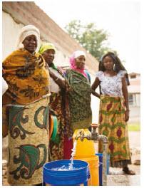 Women wait to collect water outside the maternal waiting house at Kiomboi Hospital, Iramba, Tanzania. (Photo:  WaterAid, Eliza Powell)