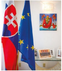 Two tables of souvenir photos, including one of the couple with Prime Minister Justin Trudeau, grace the living room. One of the tables sits next to the Slovak and EU flags. (Photo: Ashley Fraser)