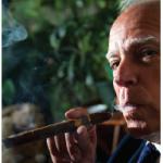 José Anselmo López Perera lights a fine Cuban cigar in the residence's smoking room. (Photo: Ashley Fraser)
