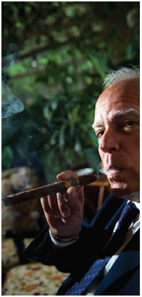 José Anselmo López Perera lights a fine Cuban cigar in the residence's smoking room. (Photo: Ashley Fraser)