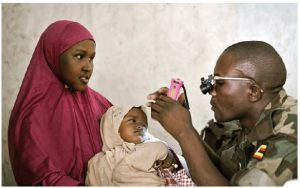 Africa's bill of health is steadily improving, thanks to medical science, special attention to chronic disease and several American philanthropic enterprises. Here, a Ugandan medic examines a young girl's eyes during an outpatient day for civilians in Mogadishu. (Photo: UN photo)