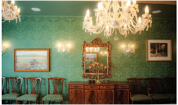 On the opposite side of the grand hall is the expansive dining room with three chandeliers, deep-green patterned wallpaper, a candelabra and a couple of small, carved wooden jewelry boxes on a sideboard. (Photo: Ashley Fraser)