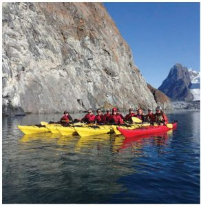 Kayakers line up in formation for  a photo break from exploring along cliffs, icebergs and the hanging glaciers high above the ocean in southern Greenland in Kangerlussuatsiaq Fjord. (Photo: Mike Beedell)
