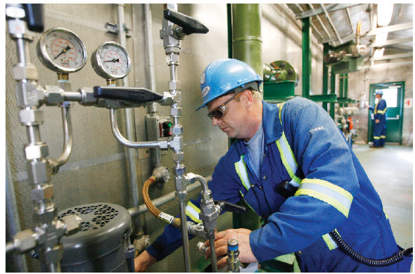Operator Dean Douthwright, of Corridor Resources, checks the methanol injection pump at a Sussex, N.B., operation that produces natural gas from shale.