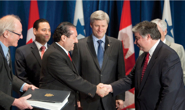 Prime Minister Stephen Harper, centre, watches as Trade Minister Peter Van Loan and Roberto Henríquez, Panama's minister of commerce and industry, sign the Canada-Panama Free Trade Agreement.