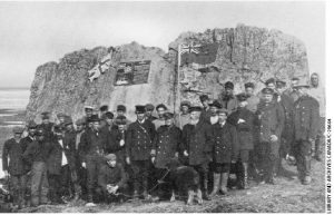 Captain Bernier (with the young muskox) claims Canada's jurisdiction at Parry's Rock by laying a plaque in July 1909.