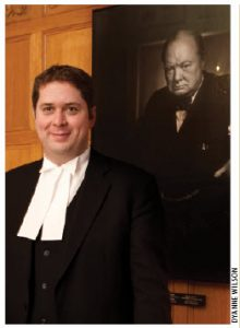 Andrew Scheer stands in front of world-renowned photographer Youssef Karsh's famous portait of British Prime Minister Winston Churchill.