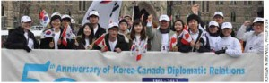 Koreans take part in the Rolling Rampage on Parliament Hill. Ambassador Nam Joo-hong is in the front row, centre, wearing a white ball cap with his hand in the air.