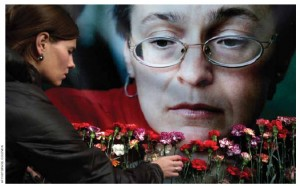 A woman places flowers before a portrait of Russian journalist Anna Politkovskaya, shot to death in her Moscow apartment building in 2006.