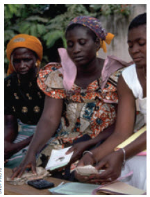 Women count money at a micro-credit lending station in Togo.