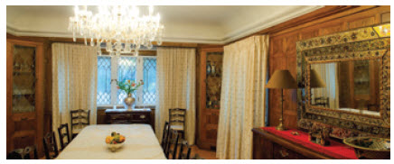 The dining room is panelled and dominated by a Peruvian mirror.