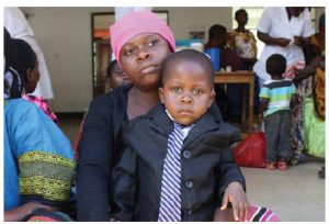 A mother brings her son to get immunized at a mobile health clinic in rural Morogoro,  Tanzania. Clinic staff provide information to mothers on how to make healthy choices when it comes to nutrition, hygiene and sanitation.