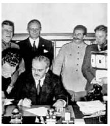 Molotov signs the Nazi–Soviet non-aggression pact. Behind him are Ribbentrop and Stalin.