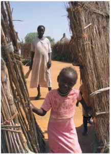 """Sudan 2008: Villagers kept their compounds clean and debris-free using the type of homemade straw brooms this mother is carrying.This photograph was taken on one of our """"show the UN flag"""" outback patrols. Jim Parker was in Sudan in 2008 as part of a UN observer mission. While there, the children stole his heart: """"I encountered a wonderful variety of children: school and working children; children looking after their baby brothers and sisters; children in dirty ragged clothing and those in clean and pressed school uniforms; begging children and laughing children and children of nomadic families and others who lived in villages."""""""