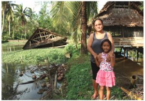 Jeniffer Inamarga and her daughter, Ruth, in front of their chicken coops. One coop was blown into a pond, drowning 600 birds and destroying this family's livelihood.