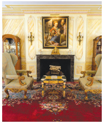 The main receiving room has a fireplace, elaborately painted crown mouldings and gold-accented furnishings.