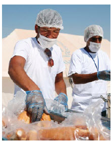 UNHCR workers serve lunch to refugees in the Akcakale camp in southern Turkey. (Photo: UNHCR A. Branthwaite)