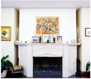 The centre of the reception area features a white marble fireplace and white furniture. A painting of horsemen with spears hangs over the mantel. (Photo: Ashley Fraser)