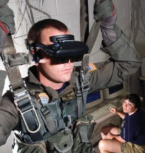 Corpsman Tim Sudduth demonstrates the Virtual Reality (VR) parachute trainer, while Aviation Survival Equipmentman Jackie Hilles controls the program from a computer console. Military personnel wear the VR glasses learn to control their movements through a series of computer-simulated scenarios.