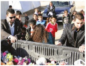 Yazidis in Iraq receive aid and toys for their children from Defend International. (Photo: Defend International)