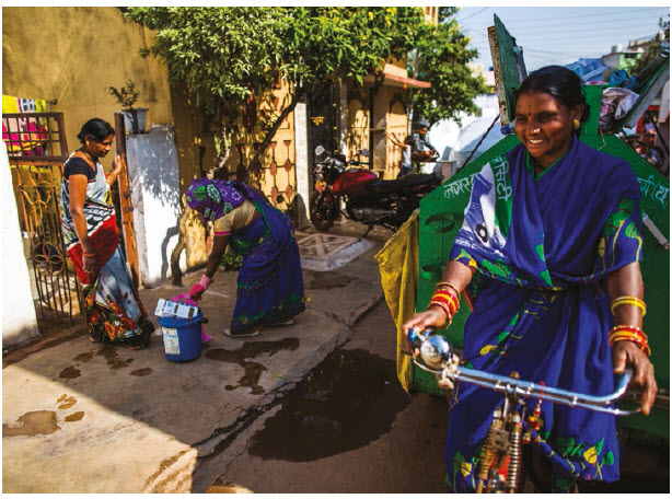 Dulari and Sushma, two sanitation and hygiene group members collect garbage from each house in ward 14, a semi-urban slum of Durg district in Chhattisgarh. (Photo: WATERAID,  PRASHANTH VISHWANATHAN)