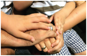A journalist, his wife, and his three children clasp hands. Now settled in a one-bedroom Air BnB in Athens, they are trying to put their lives back together while worrying about family members they had to leave behind in Turkey. (Photo: Jennifer Campbell)