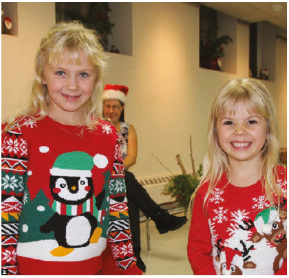 """To celebrate Estonia's 100th anniversary, Estonian children born around the world received a copy of the book Pisike puu from the government. Sisters Marin and Myrah Howe from Gatineau received their book and gifts from Estonian Christmas Father """"Jõuluvana"""" at the Ottawa Estonian Society Christmas party. (Photo: Ülle Baum)"""