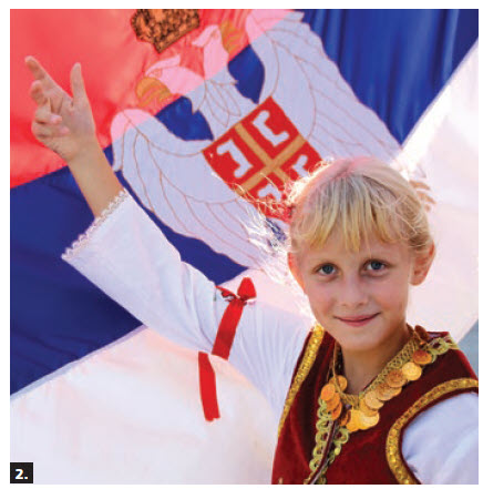 The 14th Annual Serbian Festival, featuring folklore dancing and authentic food, took place on the grounds of St. Stefan Serbian Orthodox Church. Standing next to the Serbian flag is Teodora, a member of Kolo, a Serbian folk dance group that performed at the event. (Photo: Ülle Baum)