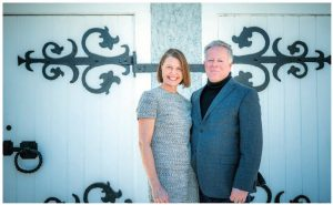 Norwegian Ambassador Anne Kari Hansen Ovind and her husband, Tom, stand in front of a former stable outside their stately residence. (Photo: Ashley Fraser)