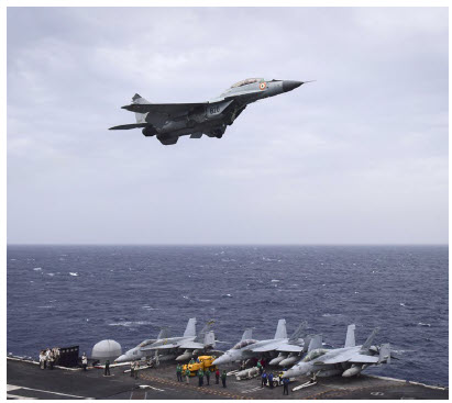 An Indian navy MIG-29K Fulcrum aircraft flies over the aircraft carrier USS Nimitz in the Bay of Bengal during Exercise Malabar between the Indian navy, Japanese maritime self-defence force and U.S. navy. It addresses shared threats to maritime security in the Indo-Asia-Pacific region. (Photo: Mass Communication Specialist 3rd Class Weston A. Mohr/U.S. Navy)