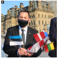 MP Jamie Schmale, chairman of the Canada-Nordic-Baltic Parliamentary Friendship Group, holds the flags of Estonia, Latvia and Lithuania. He spoke at the Baltic event. (Photo: Ülle Baum)