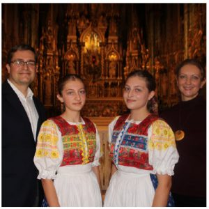 Sabina Koziakova, centre left, and Terezia Koziakova, centre right, daughters of Slovakian Ambassador Vit Koziak, far left, performed Jasna hviezdicka, a Slovakian Christmas carol. The girls are wearing handmade folk costumes and their mother, Terezia, is at right. (Photo: Sabina Koziakova, centre left, and Terezia Koziakova, centre right, daughters of Slovakian Ambassador Vit Koziak, far left, performed Jasna hviezdicka, a Slovakian Christmas carol. The girls are wearing handmade folk costumes and their mother, Terezia, is at right. (Photo: Ülle Baum)